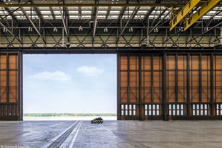 Zukunftsort TXL/Tegel: Hangar von innen mit Blick durch das offene Tor auf Freifläche und blauen Himmel.